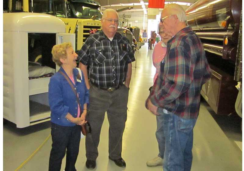 by: BARBARA SHERMAN - TALKING TRUCKS - Joyce Saari (left) co-founder of the  Pacific Northwest Truck Museum, and Terry Dovre (second from left), museum president, chat with a couple touring touring the facility during the Great Oregon Steam-Up.