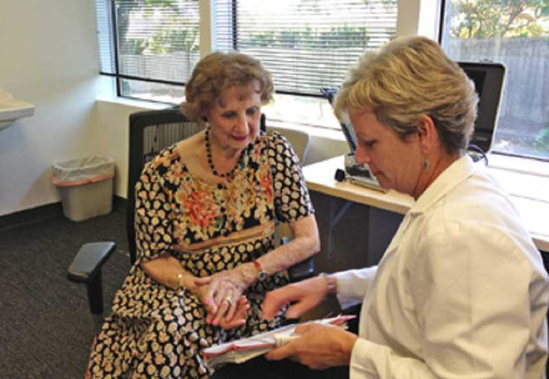 by: COURTESY OF KIM DOTSON - FOLLOW-UP IS IMPORTANT - Kim Dotson explains hearing test results to Audra Fisher, 93, during a visit to her King City office.