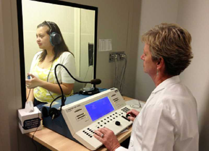 by: COURTESY OF KIM DOTSON - HIGH-TECH TESTING LEADS TO DIAGNOSIS - Kim Dotson, using her audiometer, tests the hearing of Whitney Gallup, 22, in the hearing booth in her office. Gallup, who has worn hearing aids since she was a child, graduated from college in June.