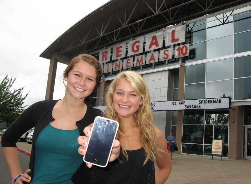 Annika Anderson, left, and Elizabeth Curtiss display the iPhone that was left inside Sherwood's Regal Cinemas early Monday morning. Police believe a maintenance worker took the phone and hid it inside wall insulation.