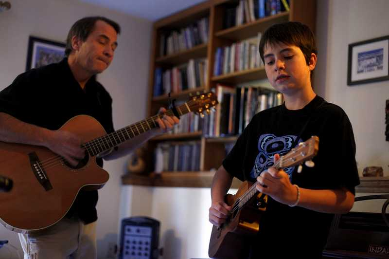 by: PHOTO BY JONATHAN HOUSE. - Jacob Walter and his father Eric, left, perform a song in their living room. As the two-man band Indalo Wind the pair have played at several private and local venues and will play at the Tigard Area Farmers Market, Sept. 16.