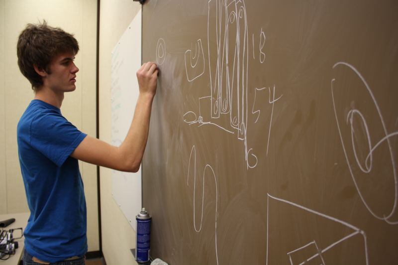 by: KATIE WILSON - Duncan Adams, a senior at St. Helens High School, sketches out different ideas for a robotic arm that would attach to the main body of a robot his team will construct in an after-school robotics class. St. Helens is the only school district to offer the class, but community members hope to start robotics teams in other school districts in Columbia County.