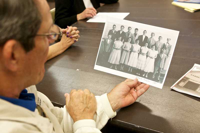 by: JAIME VALDEZ - Bob Day, who attended Garden Home School, looks at a school picture of his older brother Dean's class. The Garden Home History Project is celebrating the 1912 opening of the historic school on Saturday.