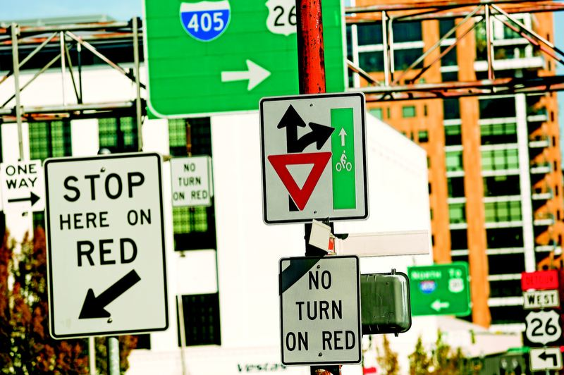by: TRIBUNE PHOTO: CHRISTOPHER ONSTOTT  - A variety of signs mark the approach to Northwest Everett and 16th, warning drivers turning right that cyclists are heading through the intersection.