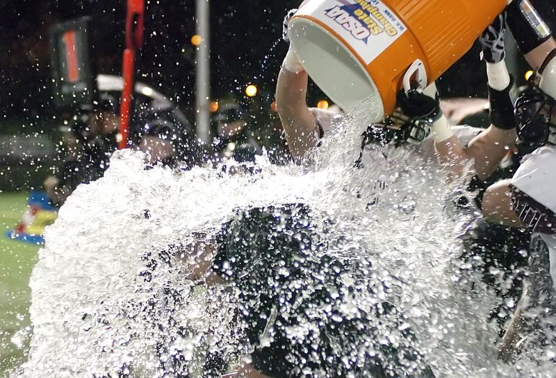 by: DAN BROOD - SPLASH ATTACK -- Sherwood defensive coordinator Wes Montgomery has a bucket of ice water dumped on him near the end of Saturday's Class 5A state championship contest.