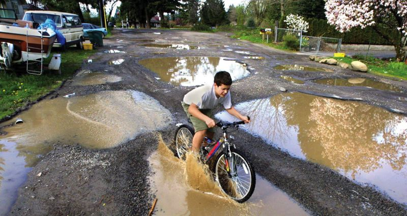 by: PORTLAND TRIBUNE FILE PHOTO - East Portland has more than its share of unpaved streets with no curbs or sidewalks, like this neighborhood near Southeast 128th Avenue and Foster Road.