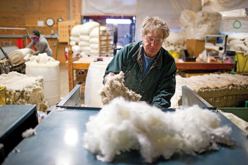 by: PAMPLIN MEDIA GROUP: CHRISTOPHER ONSTOTT - Richard Levine sorts and processes organic cotton to be used in futons at the Cotton Cloud Futons factory warehouse in Northwest Portland.