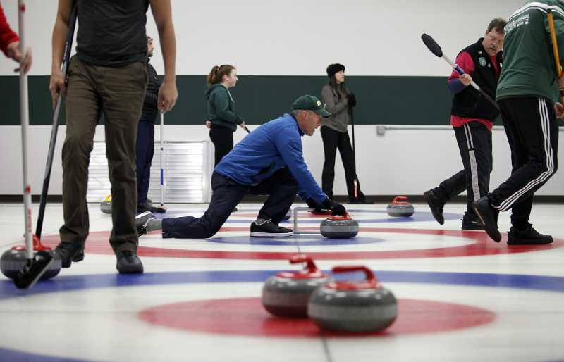 by: TIMES PHOTO: JONATHAN HOUSE - Matt Starr, center, launches a stone during a Thursday night game at the Evergreen Curling Club's new facility in Beaverton.