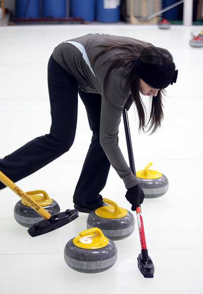 by: TIMES PHOTO: JONATHAN HOUSE - Michelle Stevens dodges other stones while sweeping at the Evergreen Curling Club.