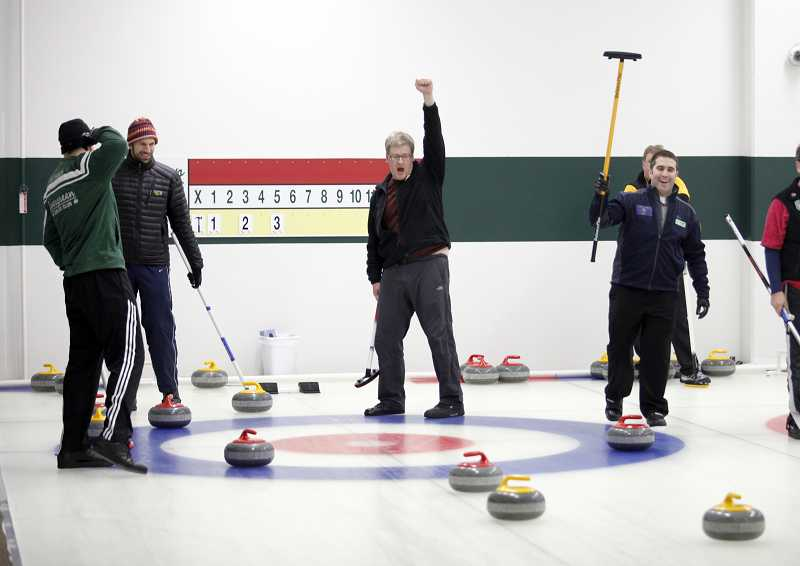 by: TIMES PHOTO: JONATHAN HOUSE - Evergreen Curling Club President Bruce Irving, center, celebrates with his teammates during a match.