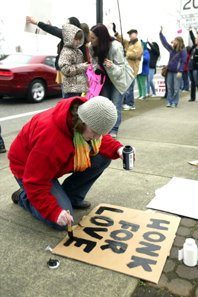by: OUTLOOK PHOTO: JIM CLARK - Mandara Nott of Portland makes a sign for the demonstration near Sweet Cakes.