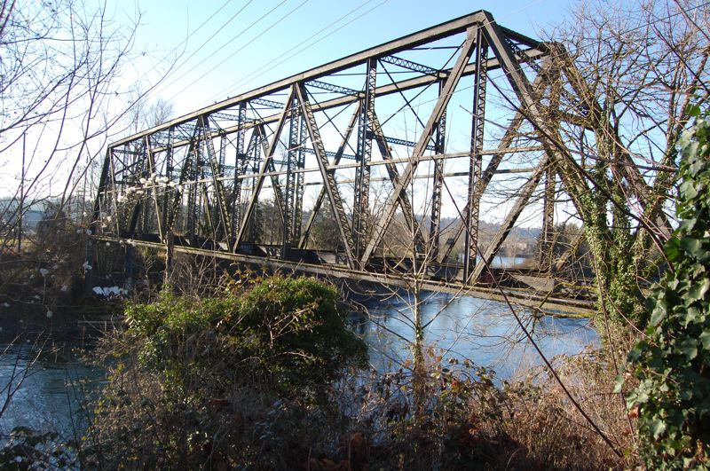by: PHOTO BY: RAYMOND RENDLEMAN - Byron Boyce and Jerry Herrmann of the Lower Clackamas River Task Force survey erosion damage imperiling the safety and stability of a railroad-owned bridge over the Clackamas River.
