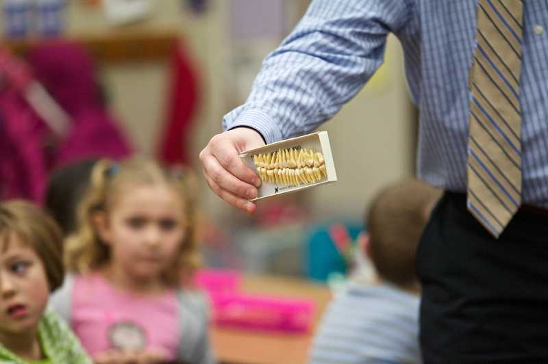 by: TIMES PHOTO: JAIME VALDEZ - Travis Evans, a dentist at Lakeside Dentistry in Tualatin, shows a box of adult teeth to the kindergartners in Danielle Wissmillers class at Byrom Elementary School. Evans visits to Tualatin elementary schools are part of National Childrens Dental Health Month.