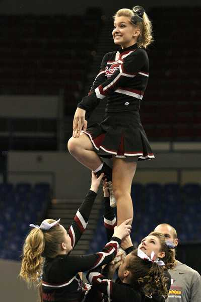 by: BRIAN MONIHAN/PAMPLIN MEDIA GROUP - UP HIGH - Ellie Hockett is hoisted in the air by Sierra Gieber, Belle Bobbitt and Megan Duricka at state competition.