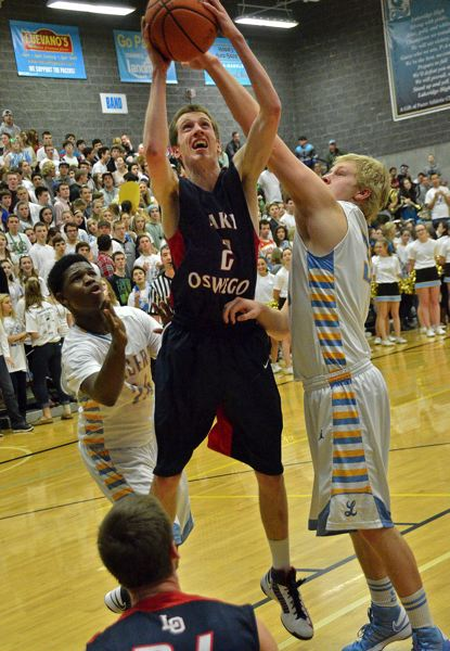 by: VERN UYETAKE - Lake Oswego Daniel Verbrug pulls down a rebound between Lakeridge's Reggie Oliver and Madison Pihl in Tuesday's victory.