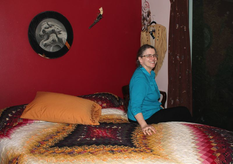 by: OUTLOOK PHOTO: ANNE ENDICOTT - Fagan's Haven owner Jane McClain sits in the Wyoming Room at her Boring bed and breakfast. A longtime quilter, McClain stitched the colorful bed covering in her on-site quilting studio.