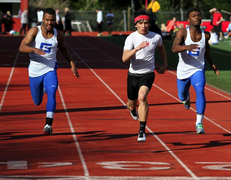 by: JONATHAN HOUSE - Oregon City senior Justin Cornejo (center) crossed the finish line first in the 100-meter dash in last weeks dual meet with Grant.