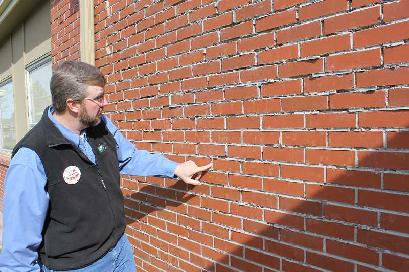 by: TONY AHERN - Dave Slaght, chairman of the Culver School Board, points out the crumbling mortar on the brick walls of Culver High School, just one of many problems the district hopes to address with a school levy.