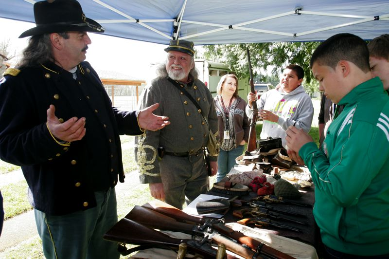 by: OUTLOOK PHOTO: JIM CLARK - Mike Tamerius, left, as a U.S. cavalry officer, and Tom Warrick, right, as a Southern cavalry officer, explain  Civil War weapons to students.