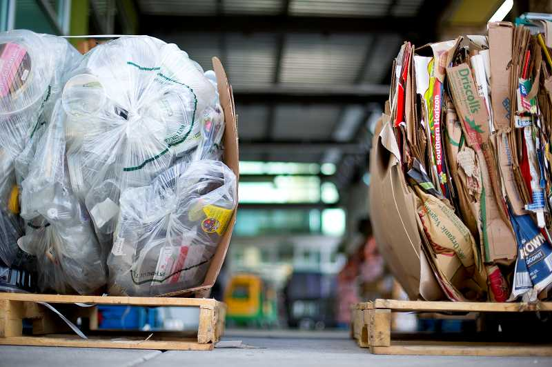 by: TIMES PHOTO: CHRISTOPHER ONSTOTT - Bundles of recyclable plastics and cardboard wait for pickup outside the Progress Ridge New Seasons store.