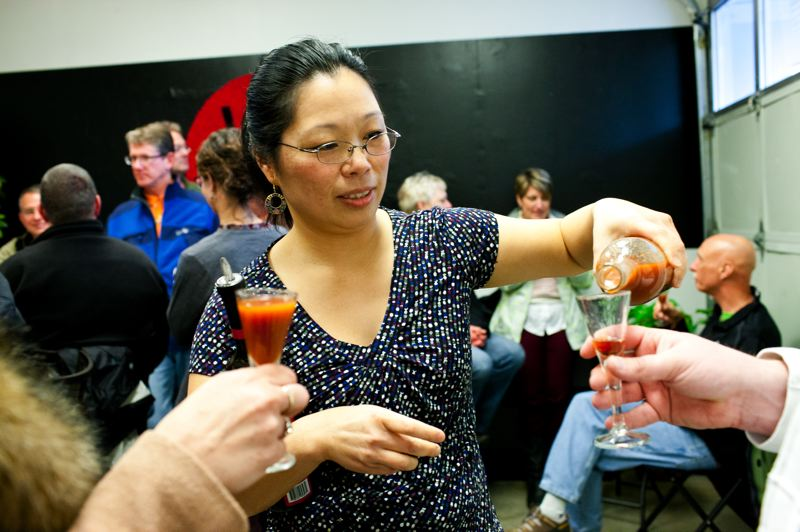 by: TRIBUNE PHOTO: CHRISTOPHER ONSTOTT - Lien Ly, co-owner of Vinn Distillery, pours samples of Mijiu Fire - a Chinese wine made from black rice - at a recent public tasting.