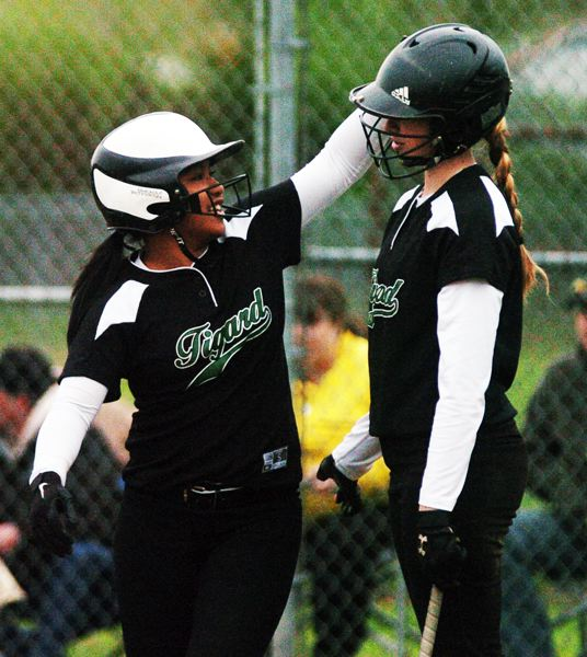 by: DAN BROOD - HAPPY TIGERS --Tigard High School freshman Kalyna Korok (left) taps teammate Emilee Heyden on the helmet after she scored a third-inning run in the Tigers' 15-1 victory over Century.