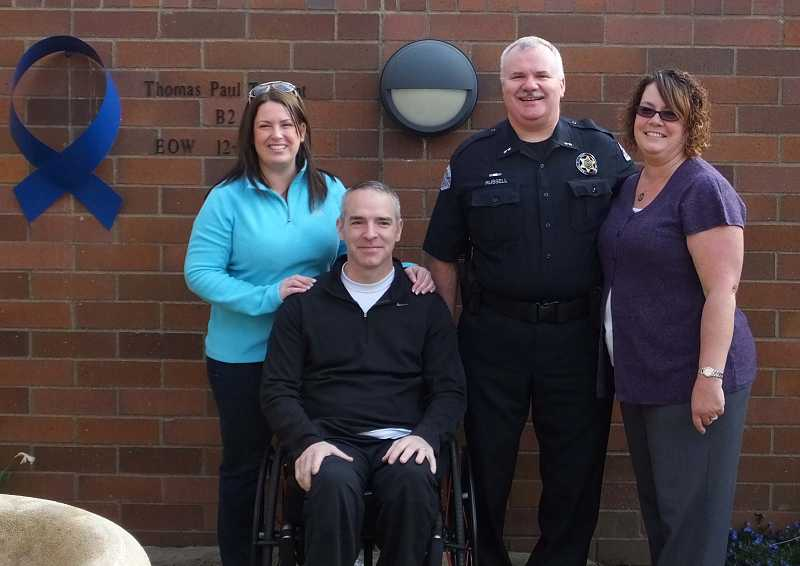 by: SUBMITTED PHOTO - Mary and Paul Meyer with Woodburn Police Chief Scott Russell and his wife, Cami.  Meyer was presented a $4,300 check to defray costs of making his home wheelchair accessible.
