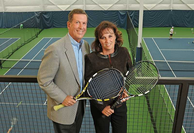 by: VERN UYETAKE - Jim and Marla Zupancic stand above the tennis courts at the Stafford Hills Club.