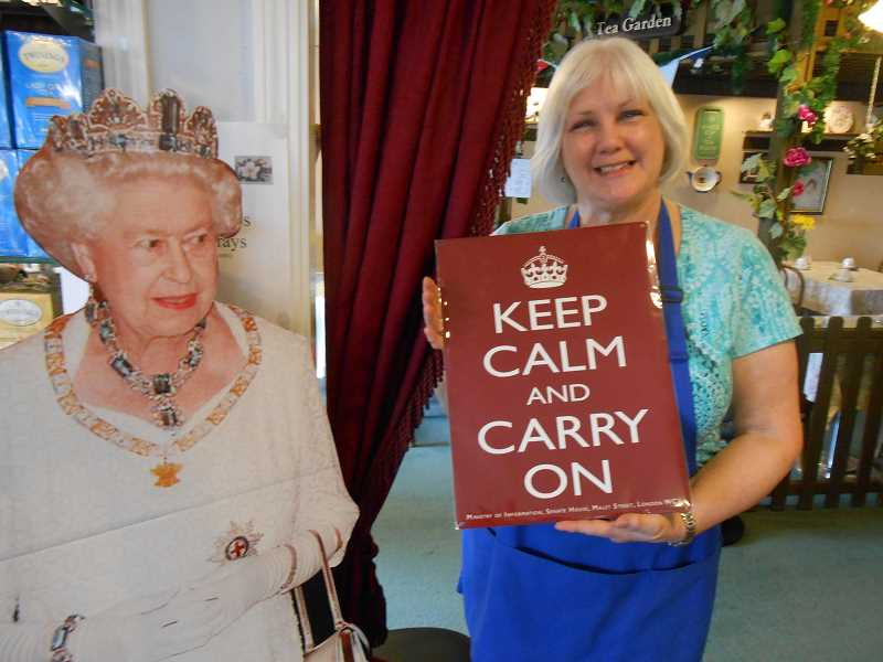 by: CLIFF NEWELL - Moya Stephens displays her philosophy of life to the evident approval of Queen Elizabeth. Customers are still treading the narrow path to Lady Di's Tea Room.