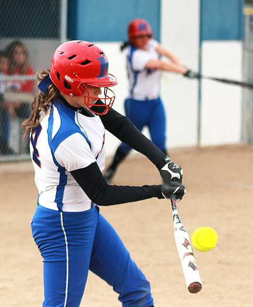 by: BILLY GATES/THE PIONEER - Madras' Sarah Brown smacks a base hit during the Buffs' 3-1 loss to La Salle Prep on Thursday at Madras High School. The loss was the third straight loss for the Buffs.