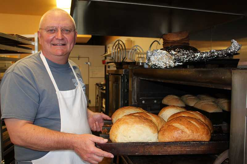 by: HOLLY M. GILL - Garry Boyd pulls freshly baked loaves of potato dill bread from the oven.