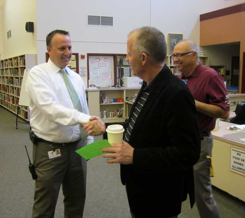 by: BARBARA SHERMAN - Ken Bell, left,  is congratulated by teacher Terrill Smith, Monday, following the announcement that he would take over as the new Sherwood High School principal.