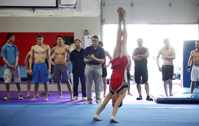 by: TIMES PHOTO: JONATHAN HOUSE - Fellow gymnasts and coaches, along with judge Doug Hills, center, look on as Patrick Casey practices his floor exercise.