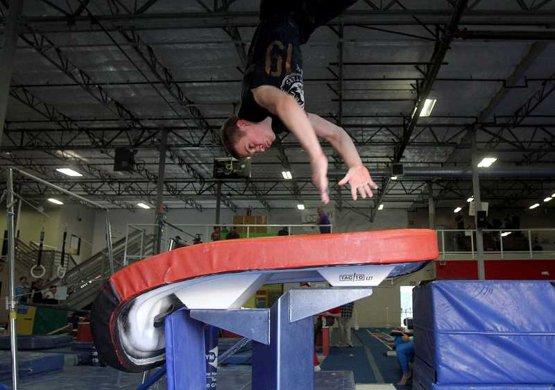 by: TIMES PHOTO: JONATHAN HOUSE - Beaverton's Josh Havelin launches himself off the vault while training Friday at the Oregon Gymnastics Academy.