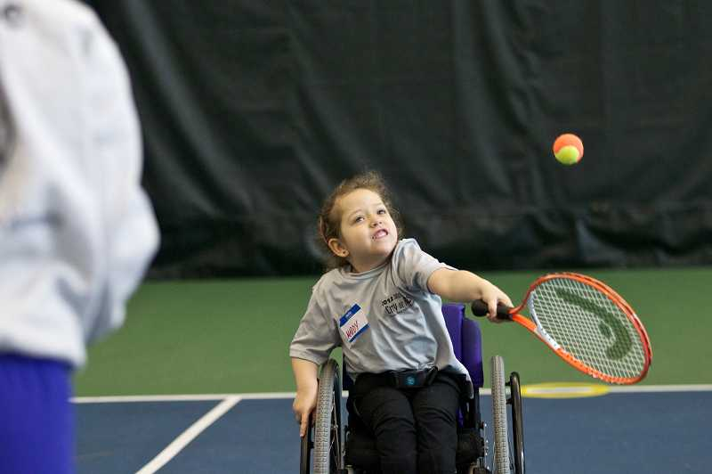 by: TIMES PHOTO: JAIME VALDEZ - Maddy Somerville, 5, of Tigard hits a tennis ball during the Northwest Wheelchair Tennis Association Wheelchair Tennis Camps for Kids at the Tualatin Hills Tennis Center.