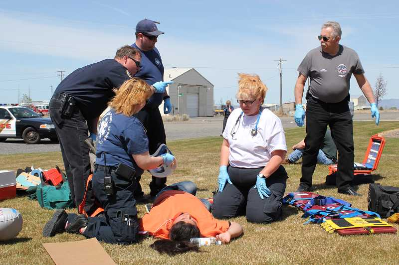 by: HOLLY M. GILL - Emergency personnel assess the 'injuries' to one of the 26 Madras High School students who portrayed injured inmates for the disaster drill.