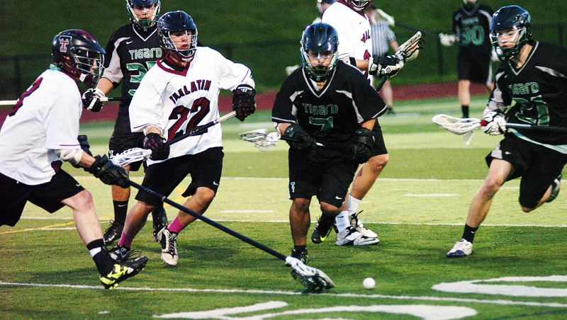 by: DAN BROOD - IT'S A BATTLE -- Tualatin's Liam McBain (22) and Tigard's Mason Worrell (7) prepare to race for the ball during last week's game played at Tualatin High School. The Timberwolves got a 6-5 victory.