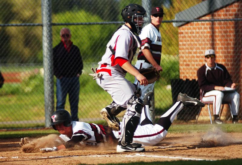 by: DAN BROOD - SLIDING IN -- Tualatin High School senior Tyler Baggenstos slides home safely behind McMinnville catcher Garret Adams during Tuesday's game. The Timberwolves scored a 4-0 victory.