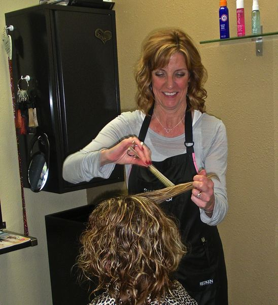 by: POST PHOTO: JIM HART - Blue Door Salon owner Kim Willis is pictured in a typical pose at her station inside a salon where five experienced professionals make people look their best.