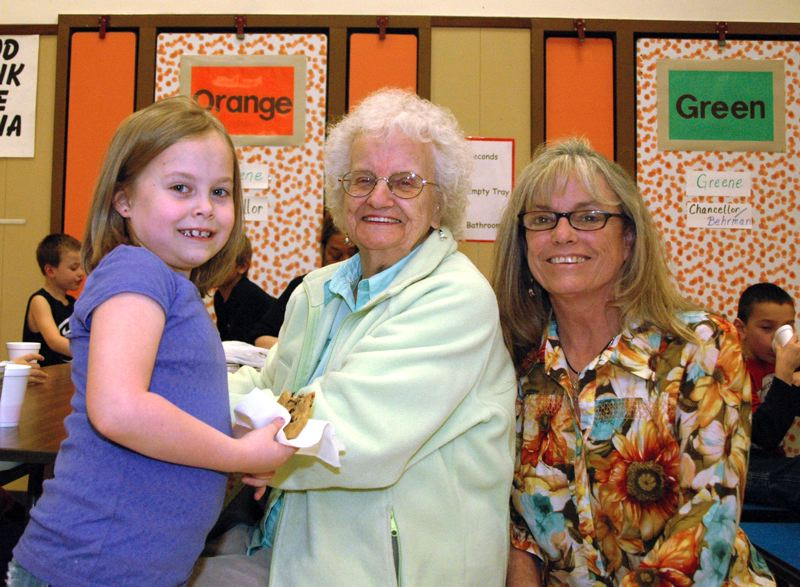 by: ESTACADA NEWS PHOTO: ISABEL GAUTSCHI - A great-grandmother, mother, and daughter enjoy juice and cookies in the cafeteria.