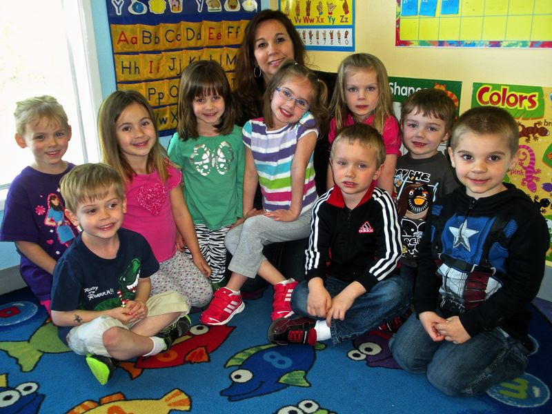 by: OUTLOOK PHOTO: JIM HART - One class at the Small World Learning Center in Gresham gathers around the day cares owner, Suzette Matthews.