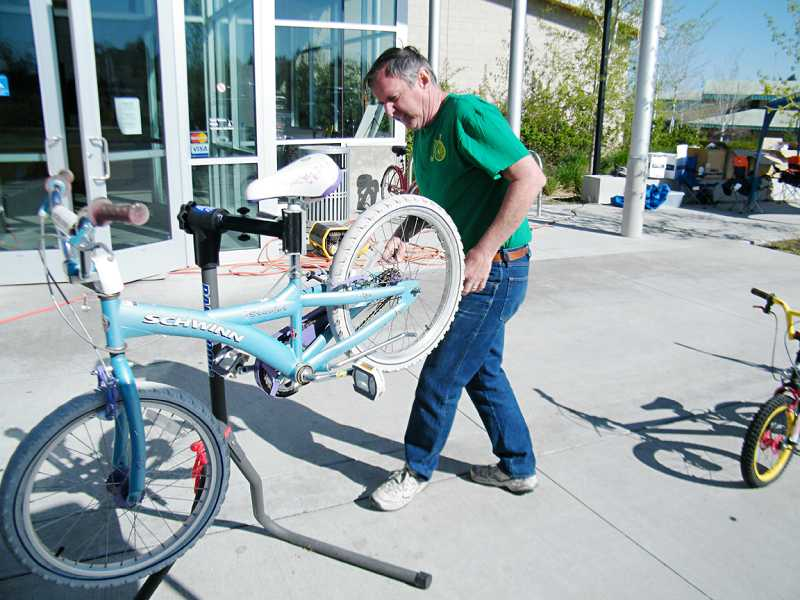 by: SUBMITTED PHOTO - A mechanic from Bicycle Re-Source of Bend tunes up a bike last Saturday. The group sent five bike mechanics to the Madras event. Les Schwab also provided two mechanics to help fix flat tires.
