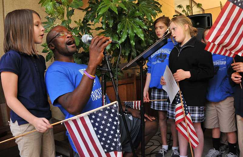by: VERN UYETAKE - Charles Patton leads the singing at LO's National Day of Prayer. Joining in are students from Our Lady of the Lake School.