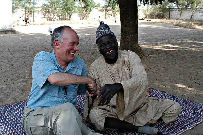 by: SUBMITTED - Bob Sanders gives a hearty handshake to his friend Cheik Fall, the chief of a village in Senegal. Sanders has built many friendships in his 15 trips to Africa.