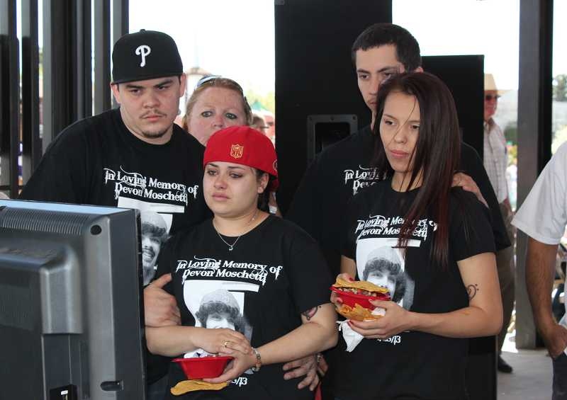 by: HOLLY M. GILL - Devon Moschetti's sister Amy (with cap), her boyfriend Eloy Pacheco (left), and friends Elias Pacheco and Mikayla Collins watch a collection of photos of Devon Moschetti during the celebration of his life at Sahalee Park in Madras on Friday.