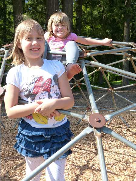 by: SUBMITTED PHOTO: ANALEIS WEIDLICH - Westridge Elementary School second-grader Julia Weidlich, front, and kindergartner Ellie Derosier play on the geodome at the school playground.