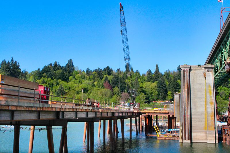 by: DAVID F. ASHTON - Although planked with wooden beams, this work bridge is sturdy enough to support a massive crane. The vertical rails installed on the old pier will support a water saw that will cut it into pieces.