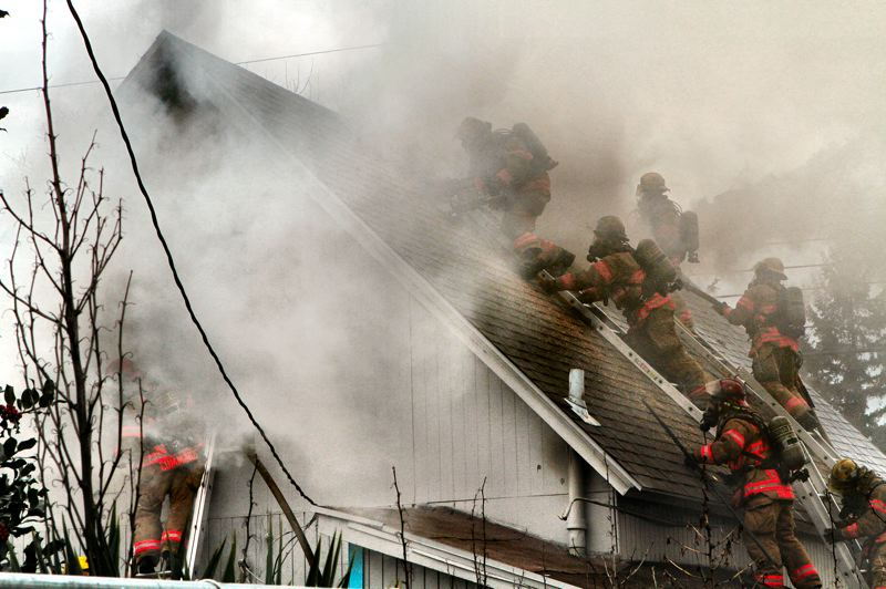 by: DAVID F. ASHTON - Thick smoke nearly hides the six crewmembers from two PF&R fire stations as they battle this Southeast Portland blaze.