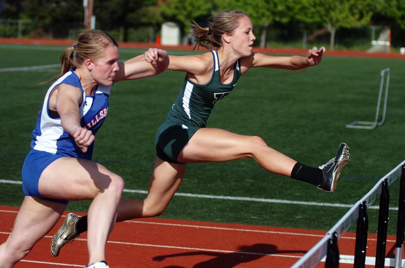 by: DAN BROOD - WHAT A RACE -- Tigard junior Lindsey Rosette (right) has an early edge on Hillsboro's Anna Dean in the 100-meter high hurdles event at last week's race.