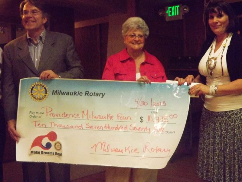 by: PHOTO COURTESY: DAVE MCDOWELL - During a ceremony at the club's weekly meeting, Heather Hobson, Milwaukie Rotary community service chairwoman, hands an oversized check to Jeff Dulcich, Providence Milwaukie Foundation board president, and Shirley Bernard, wife of Joseph M. Bernard Jr., the former Milwaukie mayor who died in June of 2012.